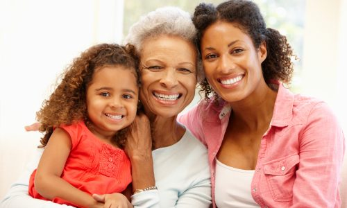 Mother,daughter and granddaughter at home smiling at the camera